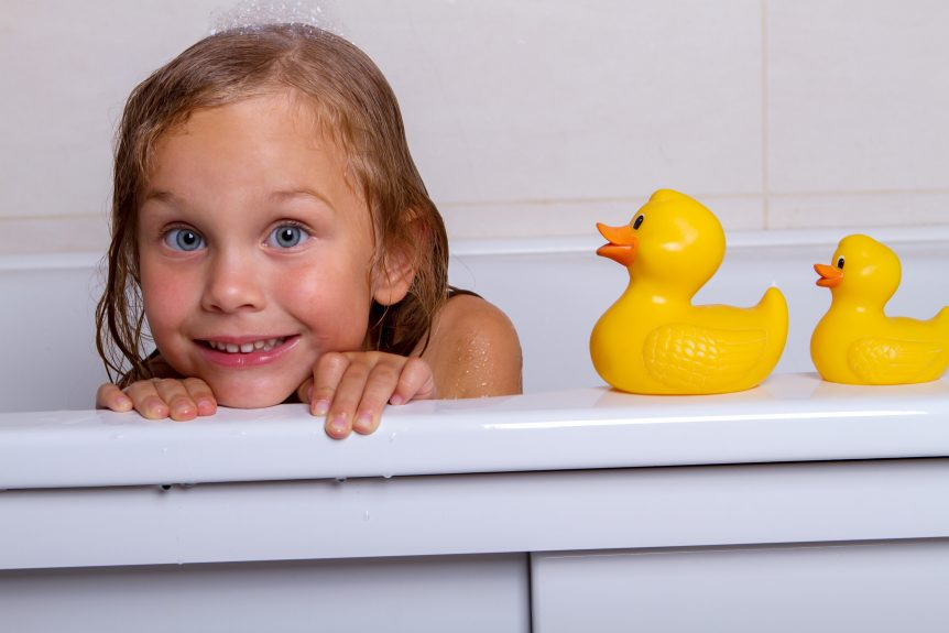 bath time fun with smiling little girl in tub with three yellow rubber ducks